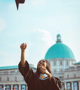 étudiante heureuse qui lance son chapeau de diplôme
